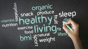 A person drawing a Healthy Living illustration with chalk on a blackboard.